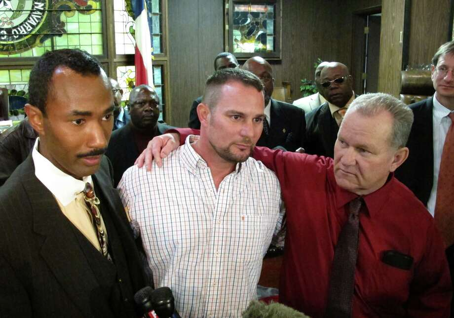 Randolph Arledge, right, embraces his son, Chris Rodgers as Innocence Project of Texas policy director Cory Session looks on after a court hearing in which Arledge was freed after three decades in prison. Photo: Nomaan Merchant, STF / AP