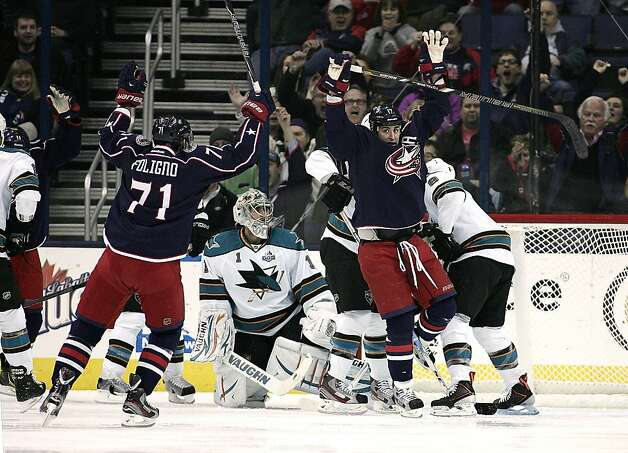 Columbus Blue Jackets' Brandon Dubinsky (17) scores against San Jose Sharks goalie Thomas Greiss (1) during the first period of an NHL hockey game, Monday, Feb. 11, 2013, in Columbus, Ohio. Rushing in to celebrate is Blue Jackets' Nick Foligno. (AP Photo/Mike Munden) Photo: Mike Munden, Associated Press