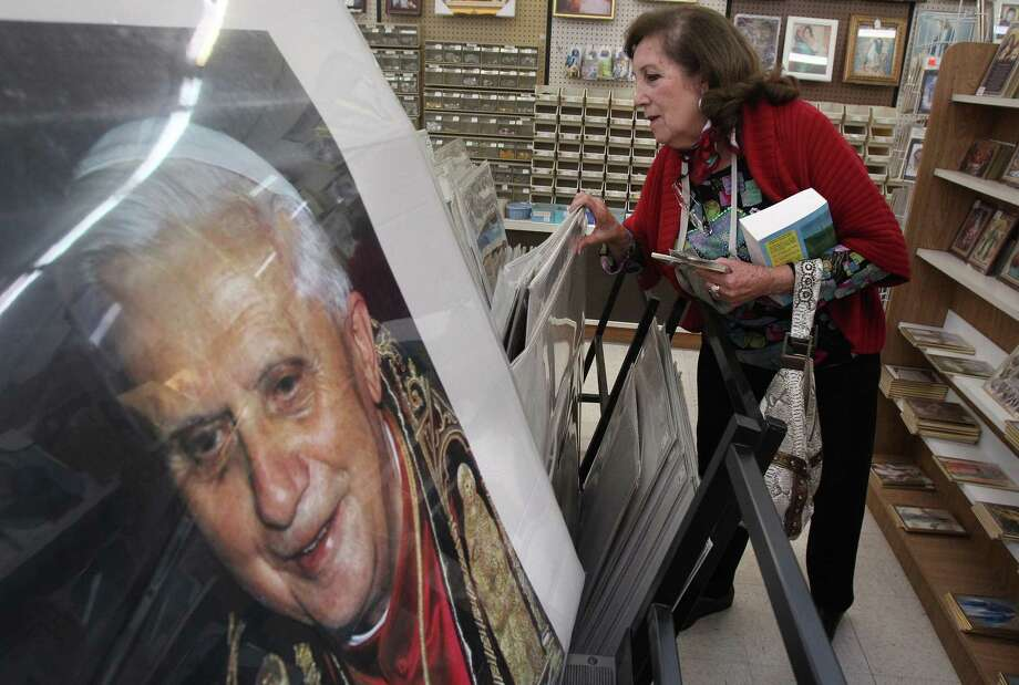 Elida Troutman browses Monday at the Sacco Catholic Bookstore, where a portrait of the pope is on display. Photo: Mayra Beltran, Staff / © 2013 Houston Chronicle