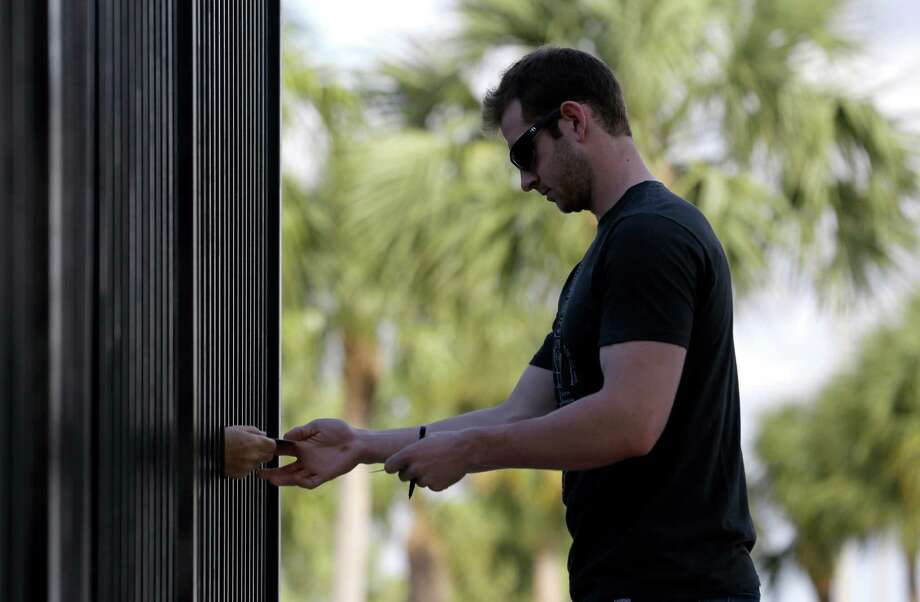 Miami Marlins first baseman Joe Mahoney signs autographs for fans staking out the team's spring training baseball facility before start of camp, Monday, Feb. 11, 2013, in Jupiter, Fla. (AP Photo/Julio Cortez) Photo: Julio Cortez