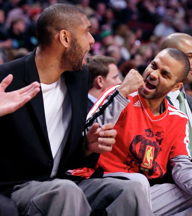 The Spurs' Tim Duncan (left) and Tony Parker react on the bench after a score against the Chicago Bulls during first half action Monday, Feb. 11, 2013 at the United Center in Chicago. Photo: Edward A. Ornelas, San Antonio Express-News / © 2013 San Antonio Express-News