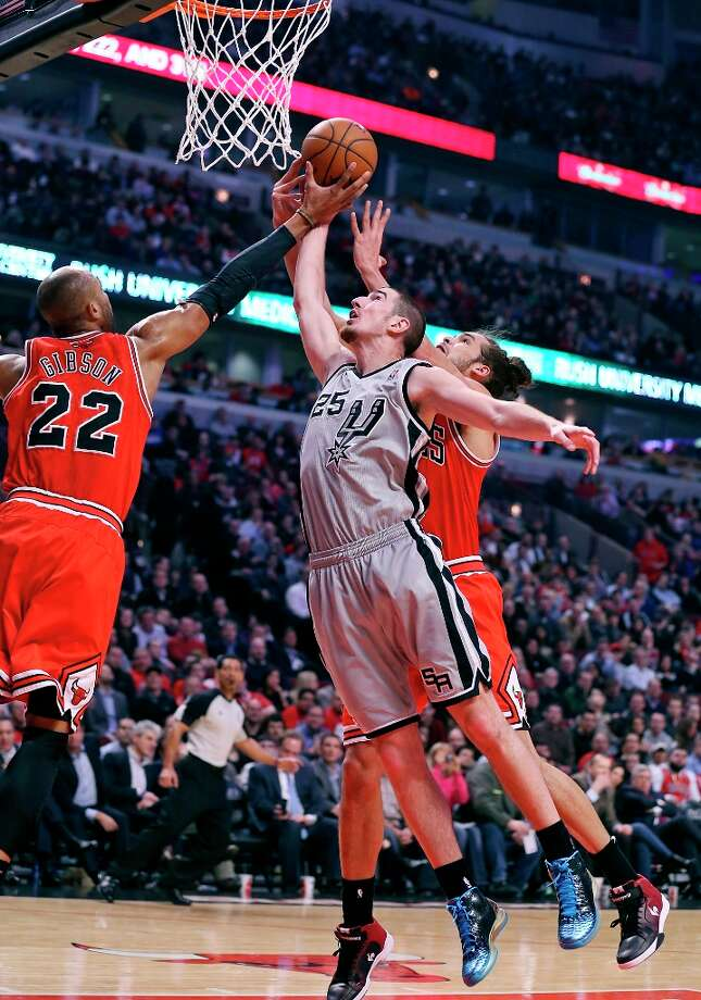 The Spurs' Nando De Colo grabs for a rebound between Chicago Bulls' Taj Gibson (left) and Joakim Noah during first half action Monday, Feb. 11, 2013 at the United Center in Chicago. Photo: Edward A. Ornelas, San Antonio Express-News / © 2013 San Antonio Express-News