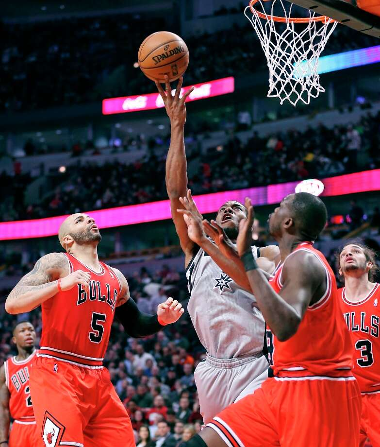 The Spurs' Kawhi Leonard shoots between Chicago Bulls' Carlos Boozer (from left) and Luol Deng during second half action Monday Feb. 11, 2013 at the United Center in Chicago. The Spurs won 103-89. Photo: Edward A. Ornelas, San Antonio Express-News / © 2013 San Antonio Express-News