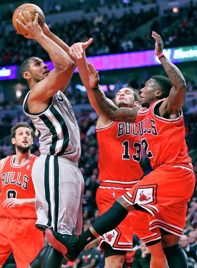 The Spurs' Boris Diaw drives to the basket against Chicago Bulls' Joakim Noah (center left) and Chicago Bulls' Nate Robinson during second half action Monday Feb. 11, 2013 at the United Center in Chicago. The Spurs won 103-89. Photo: Edward A. Ornelas, San Antonio Express-News / © 2013 San Antonio Express-News