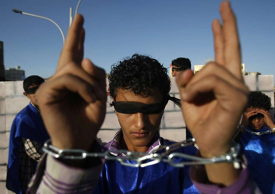 A Yemeni pro-democracy protester with covered eyes and shackled hands marches during a parade marking the second anniversary of the revolution in Sanaa, Yemen, Monday, Feb. 11, 2013. The 2011 Yemeni Revolution was as an extension of the broader Arab Spring which has toppled four authoritarian leaders to date. Yemenis were able to create a unique revolution, their struggle came peacefully, unarmed, and lead by women and youth. (AP Photo/Hani Mohammed) Photo: Hani Mohammed, Associated Press