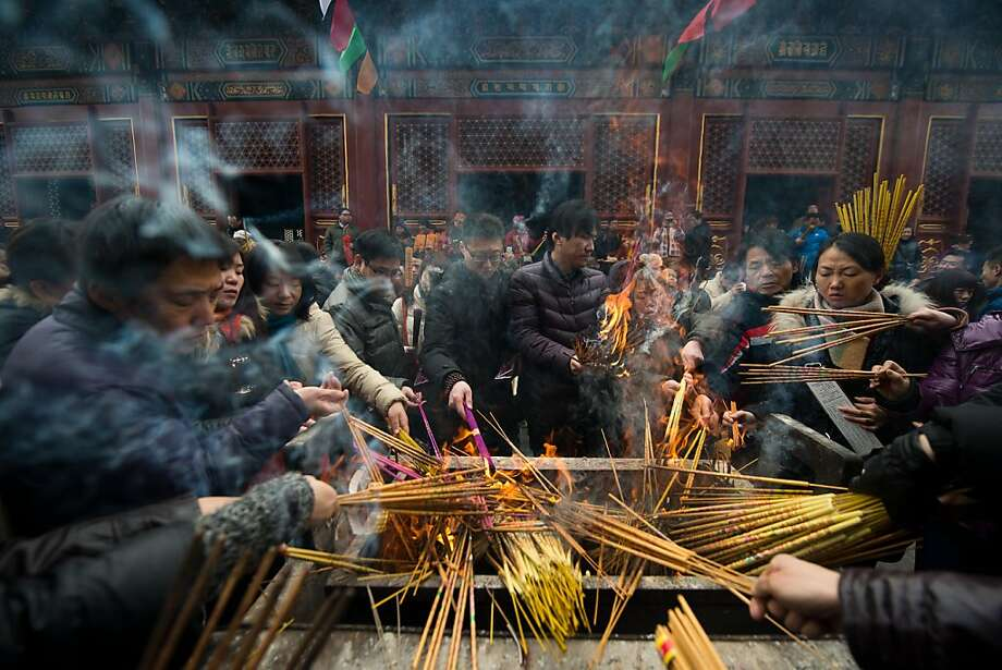 TOPSHOTS  Worshippers burn incense as part of lunar new year festivities at the Yonghegong lama temple in Beijing on February 11, 2013. A billion-plus Asians are ushering in the lunar Year of the Snake with a week of festivities. AFP PHOTO / Ed JonesEd Jones/AFP/Getty Images Photo: Ed Jones, AFP/Getty Images