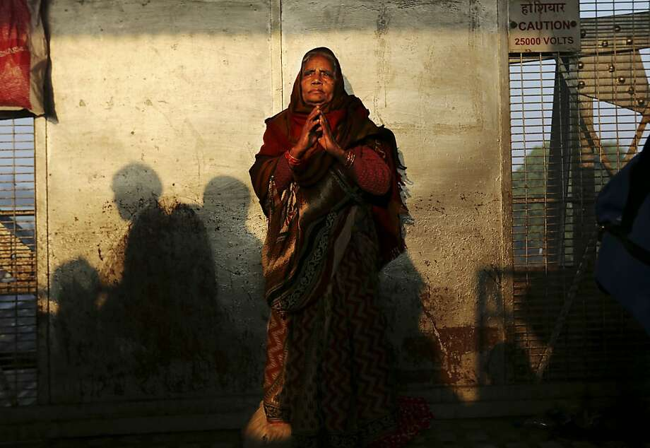 An Indian woman stands on a platform near where a stampede took place a night before, at the station in Allahabad, India, Monday, Feb. 11, 2013. The death toll from the stampede rose to 36 on Monday in the northern India city where millions of devotees had gathered for a Hindu festival that is one of the world's largest religious gatherings. (AP Photo/Kevin Frayer) Photo: Kevin Frayer, Associated Press
