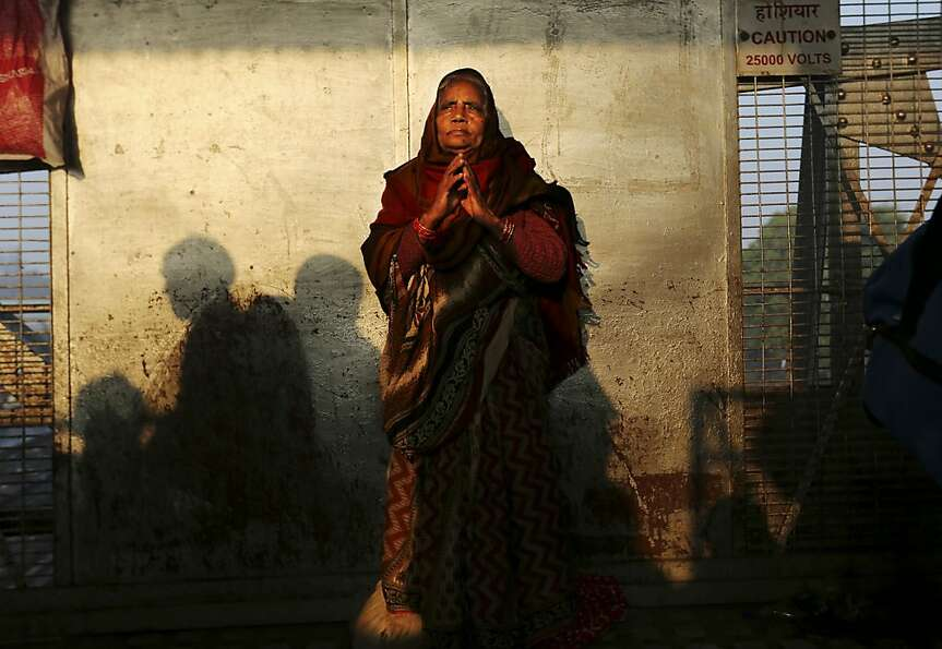 An Indian woman stands on a platform near where a stampede took place a night before, at the station