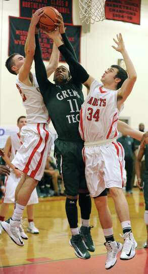 Green Tech's Jizziah Carr drives to the basket against Albany Academy's Jack Morrow, left, and Ben B
