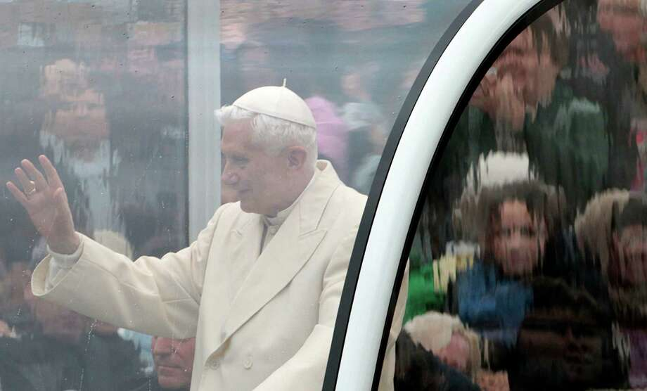 FILE - In this Wednesday, Oct. 31, 2012 file photo, Pope Benedict XVI is seen behind a window of his pope-mobile as he delivers his blessing to faithful gathered in St. Peter's Square for his general audience, at the Vatican. Benedict always cast himself as the reluctant pope, a shy bookworm who preferred solitary walks in the Alps to the public glare and the majesty of Vatican pageantry. But once in office, he never shied from charting the Catholic Church on the course he thought it needed _ a determination reflected in his stunning announcement Monday that he would be the first pope to resign since 1415. (AP Photo/Gregorio Borgia) Photo: Gregorio Borgia