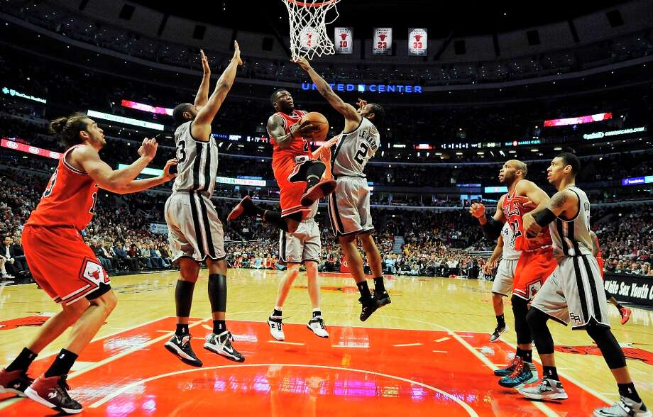 The Bulls' Nate Robinson (center) drives to the basket between the Spurs' Boris Diaw (center left) and Kawhi Leonard during second half action Monday Feb. 11, 2013 at the United Center in Chicago. The Spurs won 103-89. Photo: Edward A. Ornelas, San Antonio Express-News / © 2013 San Antonio Express-News