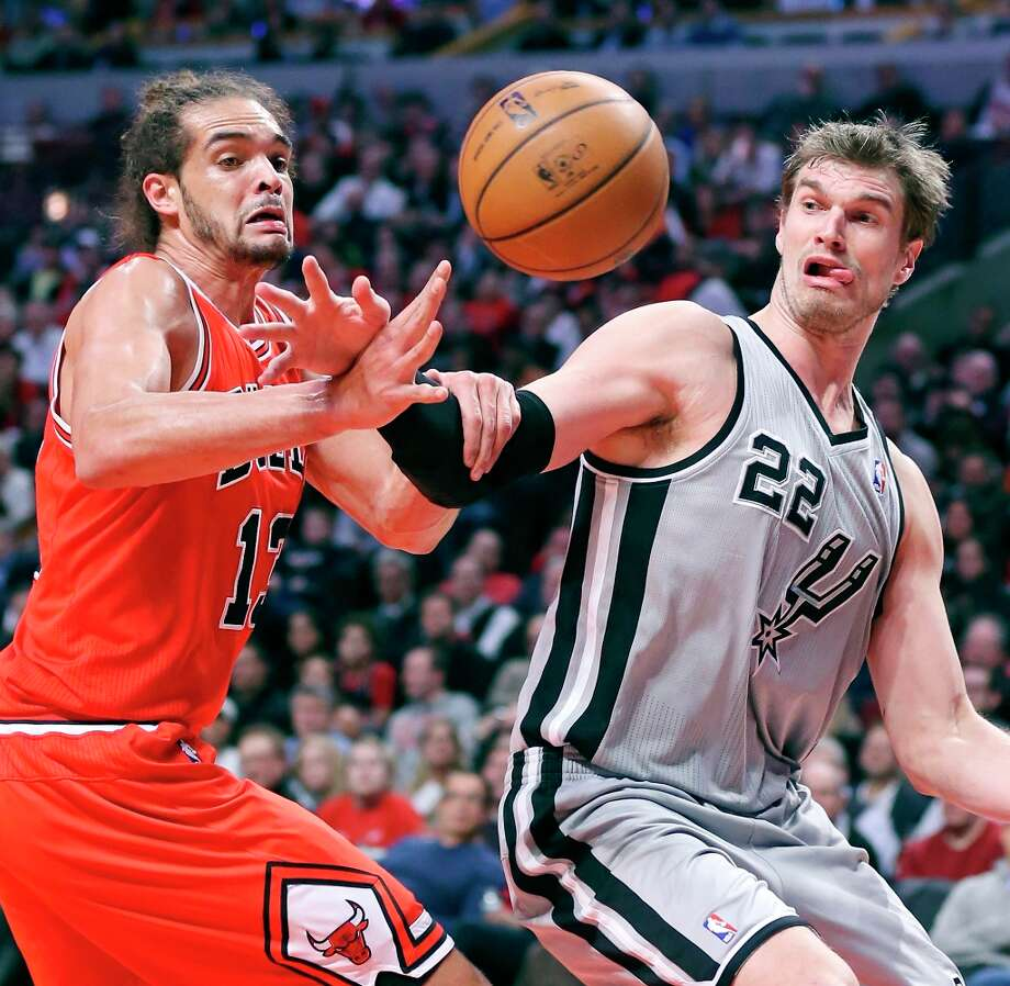 The Bulls' Joakim Noah (left) and Spurs' Tiago Splitter grab for a loose ball during second half action Monday Feb. 11, 2013 at the United Center in Chicago. The Spurs won 103-89. Photo: Edward A. Ornelas, San Antonio Express-News / © 2013 San Antonio Express-News
