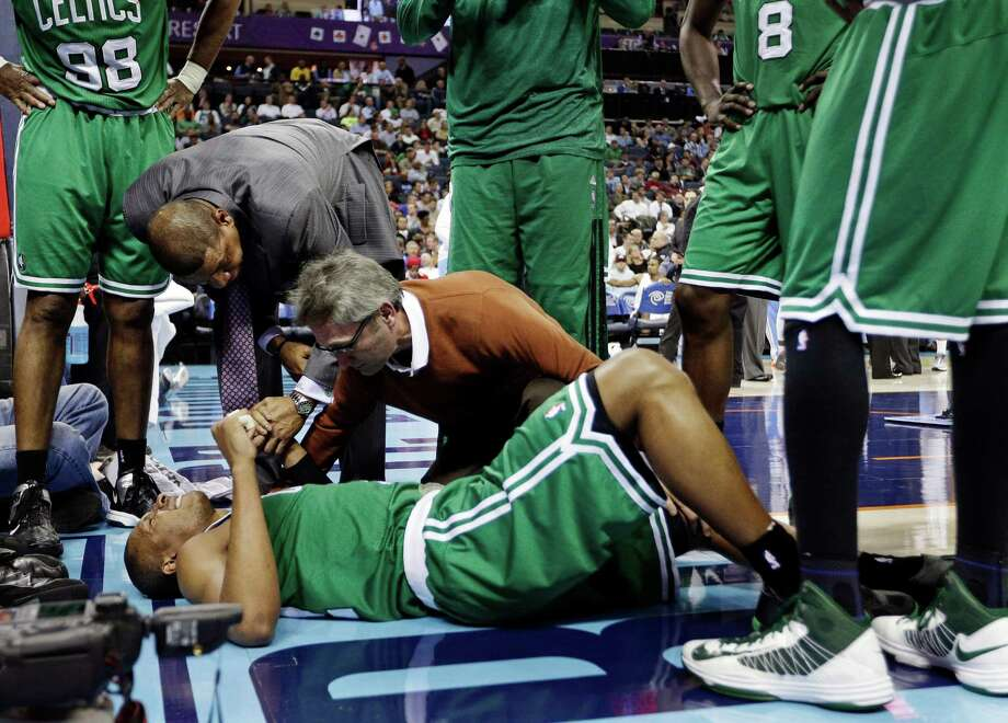 Celtics coach Doc Rivers consoles Leandro Barbosa, bottom, as a trainer examines him. The Celtics could lose Barbosa, who has filled in well for Rajon Rondo. Photo: Chuck Burton, STF / AP