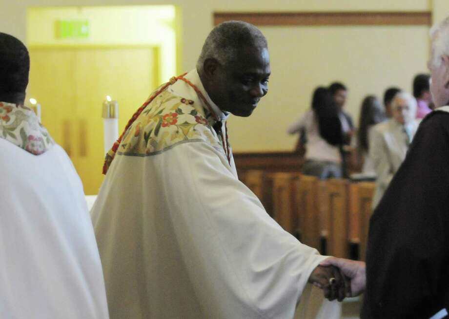 Cardinal Peter Turkson, left, a native of Ghana, reaches out to shake hands as they exchange the sign of the peace during service at St. Mary of the Angels Chapel on the campus of Siena College on Sunday, May 20, 2012 in Loudonville, NY.  The service was held for the nonprofit organization, Medicus In Christi, started by Dr. Joseph Marotta, a Siena graduate and the orthopedic surgeon for the college's athletic program.  The nonprofit was set up to help the people of Ghana.  (Paul Buckowski / Times Union) Photo: Paul Buckowski / 00017756A