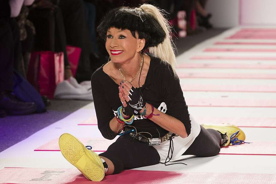 Designer Betsey Johnson greets the audience with her trademark cartwheel and split following a showing of her Fall 2013 collection during Fashion Week in New York, Monday, Feb. 11, 2013. (AP Photo/John Minchillo) Photo: John Minchillo, Associated Press