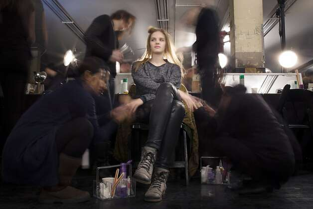 In this photo made with a long exposure, a model is prepared backstage before the Theyskens' Theory Fall 2013 collection is shown during Fashion Week, Monday, Feb. 11, 2013, in New York. (AP Photo/John Minchillo) Photo: John Minchillo, Associated Press
