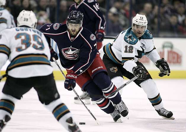 Columbus Blue Jackets' Nick Foligno (71) races through San Jose Sharks defenders Logan Couture (39) and Patrick Marleau (12) during the second period of an NHL hockey game, Monday, Feb. 11, 2013, in Columbus, Ohio. (AP Photo/Mike Munden) Photo: Mike Munden, Associated Press