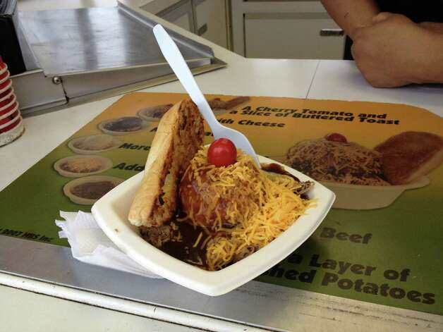 A beef sundae gets served up at the food court at the San Antonio Stock Show & Rodeo. A beef sundae consists of a scoop of mashed potatoes, gravy, chopped roast beef and cheddar cheese, all topped with a cherry tomato and a side of Texas toast. Photo: Sarah Tressler,  San Antonio Express-News