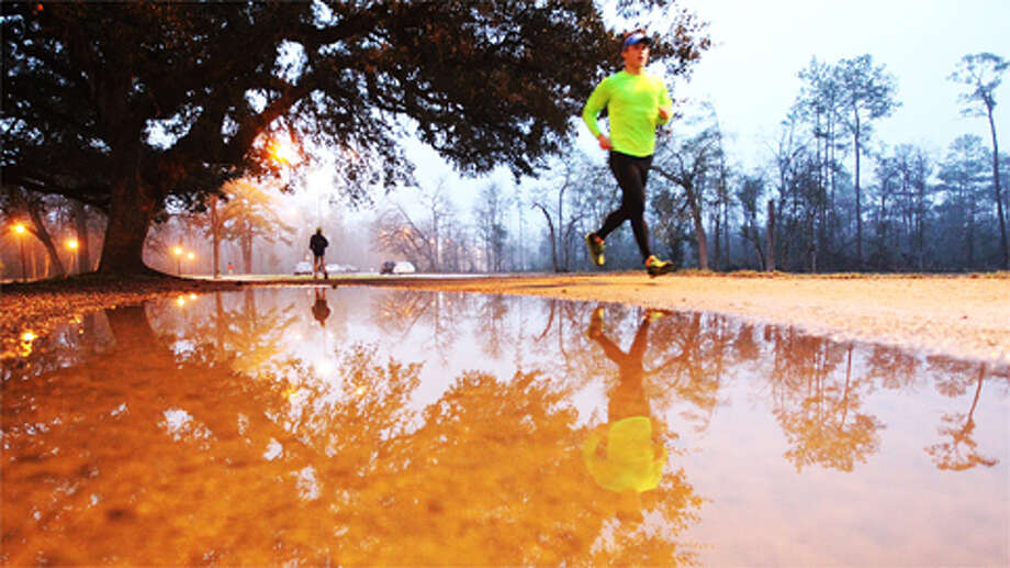 Runners and walkers make their way along a trail spotted with puddles from recent rains on a damp hazy Tuesday morning, Feb. 12, 2013, in Houston. Photo: Nick De La Torre, .