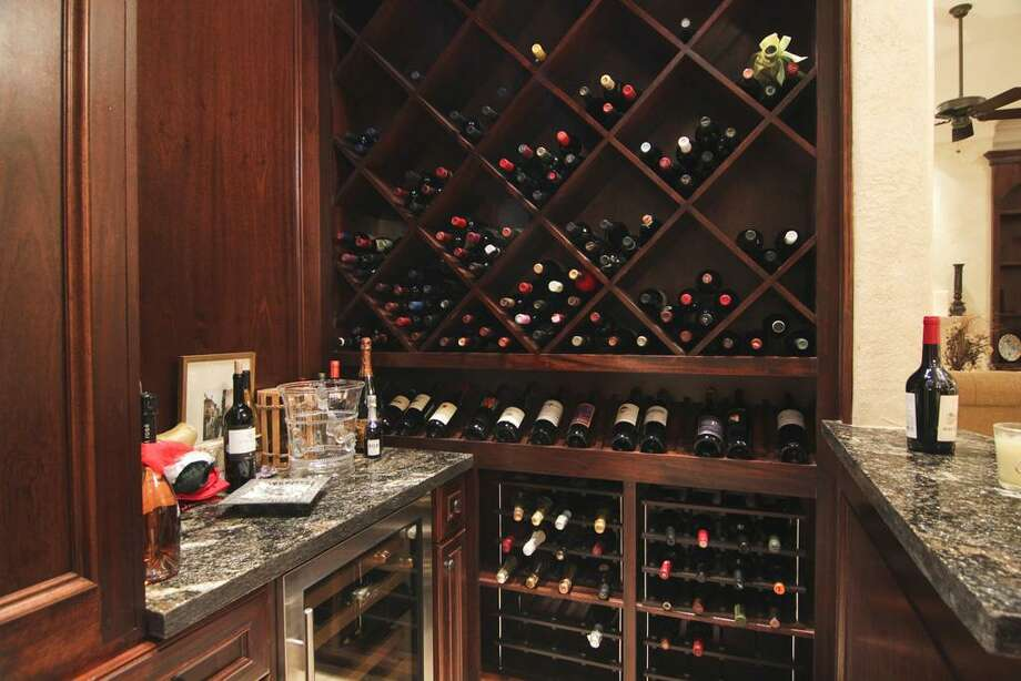 Rich and elegant walk-in wine bar perfectly located in the center of the house. Mahogany paneled walls & shelves. Granite counters and a built-in wine cooler. Photo: Martha Turner Properties
