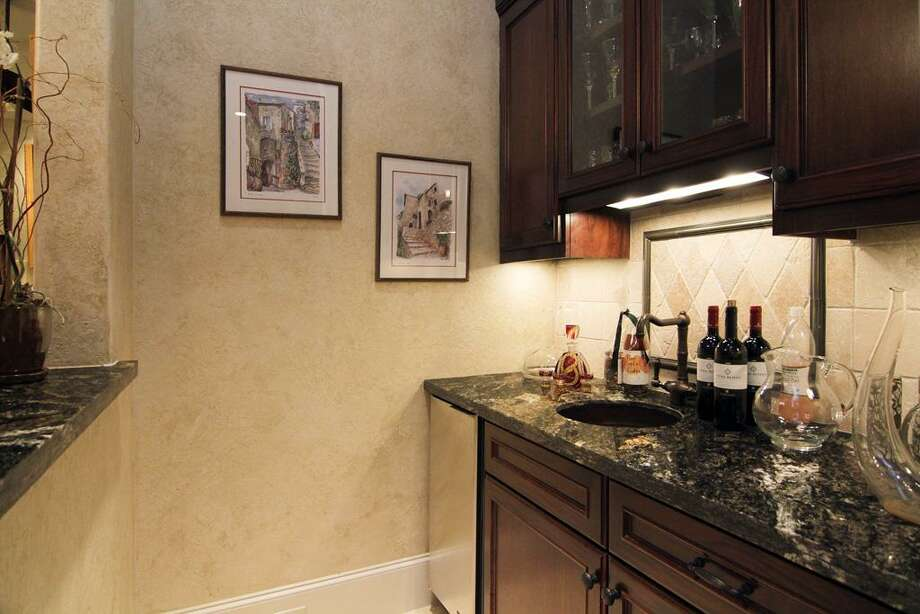 The wine room is a walk-in wet bar, with granite counters, tumbled travertine marble back-splash & floors. Built in ice maker and under counter lighting. Photo: Martha Turner Properties
