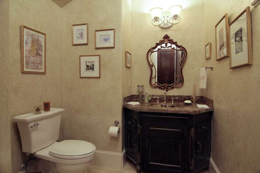 The powder room is located in a nice private area of the home. Note the leather type look on the gra