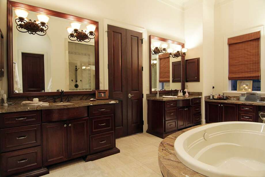 His and her dressing areas and a sit down make up area all with mahogany cabinets. Tumbled travertine marble floors and a leather looking granite create that luxury country club feeling. Photo: Martha Turner Properties