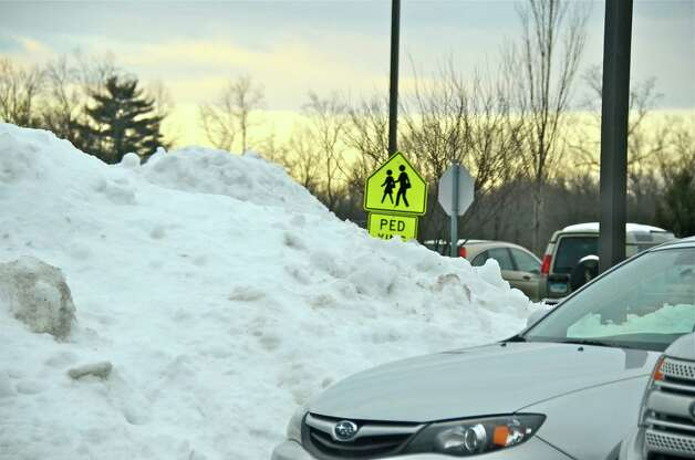 New Canaan Public Schools reopened this morning after a four-day weekend thanks to the blizzard. Above, mounds of snow fill the parking lot at New Canaan High School. Photo by Jeanna Petersen Shepard  Feb. 12, 2013 Photo: Freelance Photo