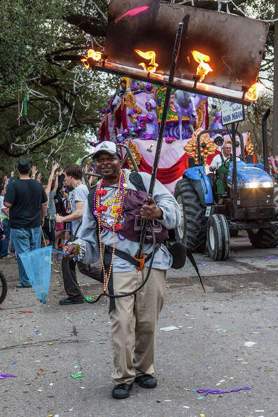 Flambeaux carrier in the 2013 Krewe of Bacchus Mardi Gras Parade on February 10, 2013 in New Orleans