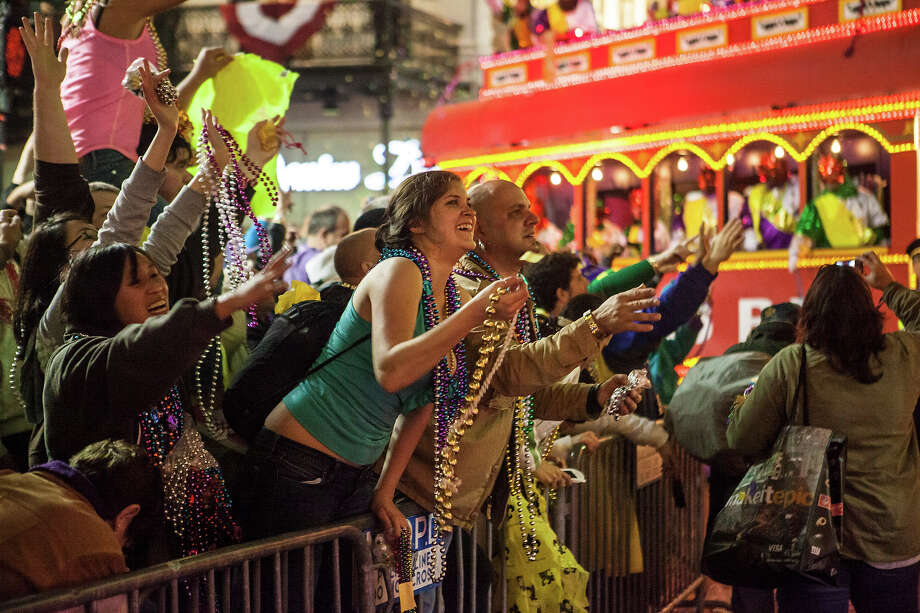 Fans and revelers catch beads tossed by the riders in the 2013 Krewe of Orpheus Mardi Gras Parade on February 11, 2013 in New Orleans, Louisiana. Photo: Skip Bolen, Getty Images / 2013 Skip Bolen