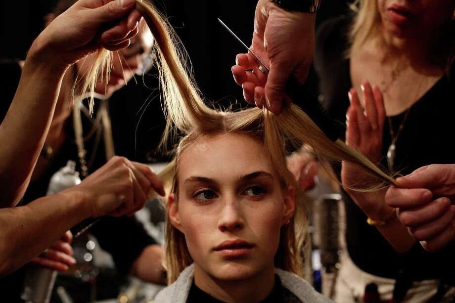 A model has her hair styled before wearing a design by Kaufmanfranco during the Mercedes-Benz Fashion Week Fall 2013 collections on February 11, 2013 in New York.    AFP PHOTO/Joshua LOTTJoshua LOTT/AFP/Getty Images Photo: JOSHUA LOTT, Stringer / 2013 AFP