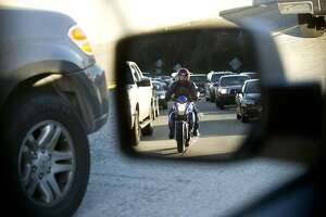Seen reflected in a side mirror, a motorcyclist lanesplits during evening commute on Highway 24 on Friday, Feb. 8, 2013, in Oakland, Calif.