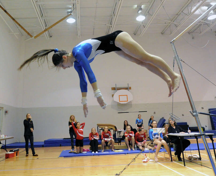 Anna Violette of Staples dismounts off the uneven bars during the girls gymnastics meet between Staples High School and Greenwich High School at the YWCA in Greenwich, Thursday afternoon, Jan. 17, 2013. Photo: Bob Luckey / Greenwich Time