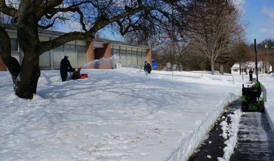 Ground crews clears sidewalks and entrances Tuesday afternoon at Osborn Hill Schools, as officials aim to reopen schools Wednesday after having been closed three days by the blizzard.  FAIRFIELD CITIZEN, CT 2/12/13 Photo: Genevieve Reilly / Fairfield Citizen