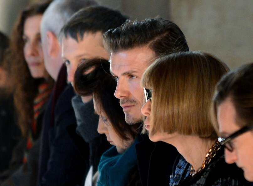 David Beckham (C) sits next to Vogue magazine editor Anna Wintour (2nd-R) at the Victoria Beckham sh