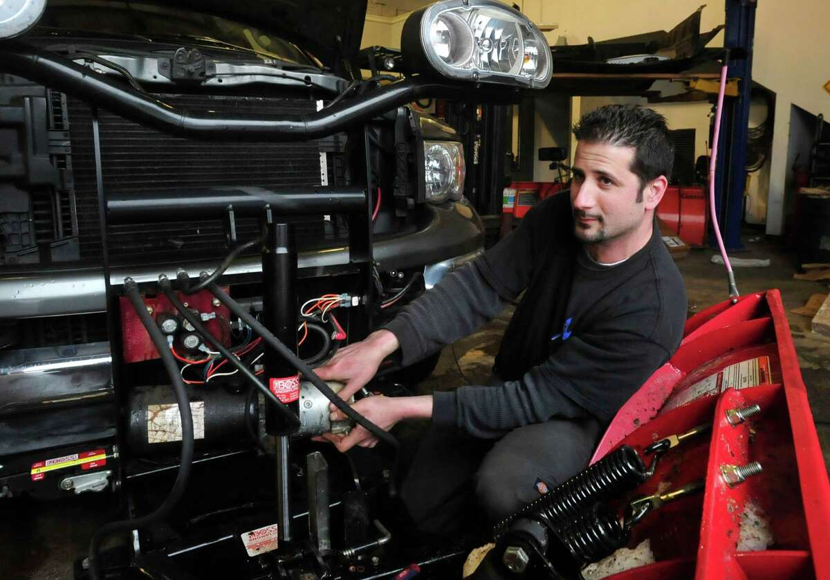 Greg Saltz changes the motor on a plow at Ness Automotive, his family business in Danbury Monday, Feb. 11, 2012.