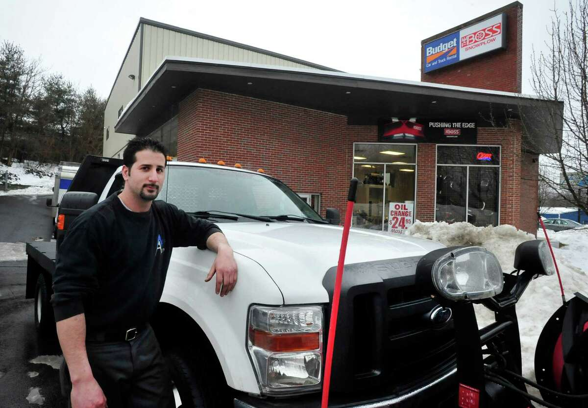 Greg Saltz stands by the truck he drives when he picks employees up for work in severe weather at Ness Automotive, his family business, in Danbury Monday, Feb. 11, 2012.