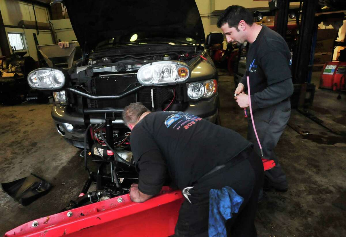 Greg Saltz, right, works changing the motor on a plow at Ness Automotive, his family business in Danbury Monday, Feb. 11, 2012.