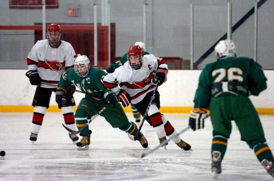 Byram, Dec. 28, 2009.  GHS #11, Joey Lodato, center, behind him is Trinity Catholic #12 Chris Lambronakos, and GHS #7, far left, Woody Waesche at hockey game the Dorothy Hamill Skating Rink. Photo: Helen Neafsey, Helen Neafsey/staff Photographer / Greenwich Time