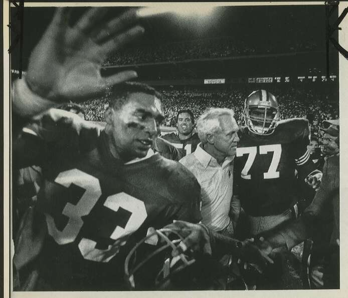23 JAN 89 - Roger Craig (L), Coach Bill Walsh (left center) and Bubba Paris leave the field after a