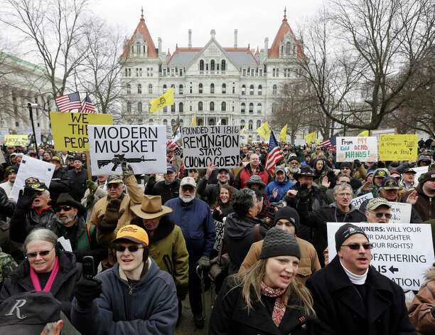 People hold signs during a Turn Albany Upside Down rally at the Capitol on Tuesday, Feb. 12, 2013, in Albany, N.Y. Hundreds of opponents of the state's new gun control law say it infringes on their right to bear arms, criticizing Gov. Andrew Cuomo and legislators, chanting for freedom and taking a collective oath to uphold the constitution. Photo: Mike Groll, AP / AP