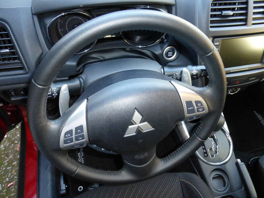 Note the silver-colored paddle shifters behind the wheel.