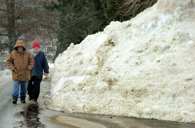 Richard Schrack, left, and Arthur Wetmore, of Danbury, walk on Hayestown Road in Danbury, Conn., Tuesday, Feb. 12, 2013,  passing heaps of snow, left over from the recent blizzard. Photo: Carol Kaliff / The News-Times