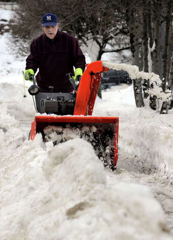 Antonio Lourenco uses a snowblower to clear a walk near the North Street Shopping Center in Danbury, Conn. Tuesday, Feb. 12, 2013.  A blizzard dumped almost 2 feet of snow on the area late last weekend. Photo: Carol Kaliff / The News-Times