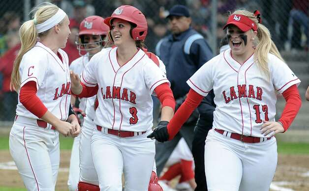 Lamar players Casey Cromwell, left, and Alyssa Burnett, right, congratulate Candyce Carter, center, on her home-run during the Lamar University softball game against UTSA at Ford Park on Saturday, February 9, 2013.  Lamar won over UTSA 3-2. Photo taken: Randy Edwards/The Enterprise