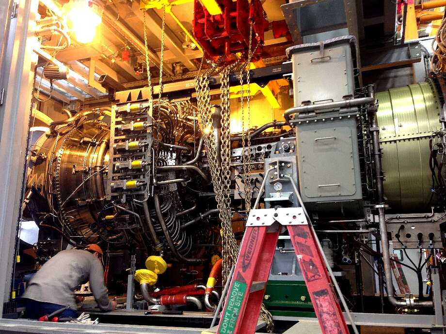 A GE Energy plant employee in Houston works to assemble a natural gas-powered aeroderivative turbine system. The completed unit will be part of a GE Energy line with models that have the capacity to generate 16 megawatts and 125 megawatts of electricity. The units can be turned on within 10 minutes. They can run on natural gas and other fuels, like ethanol.