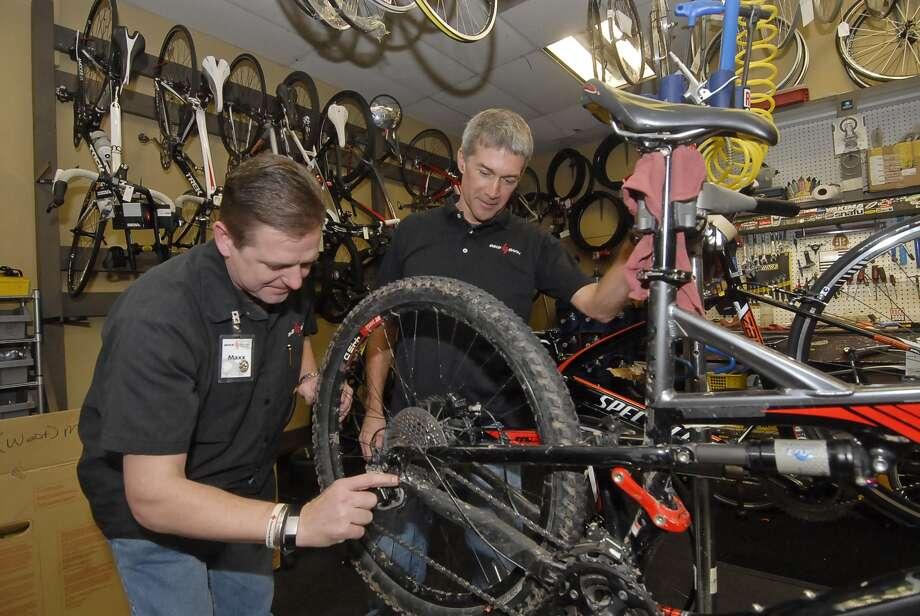 "Bike Barn owner Neil Bremner watches employee Maxx Lewis ""true"" a bike's back wheel. Photo:  Tony Bullard 2012, Freelance Photographer / © Tony Bullard & the Houston Chronicle"