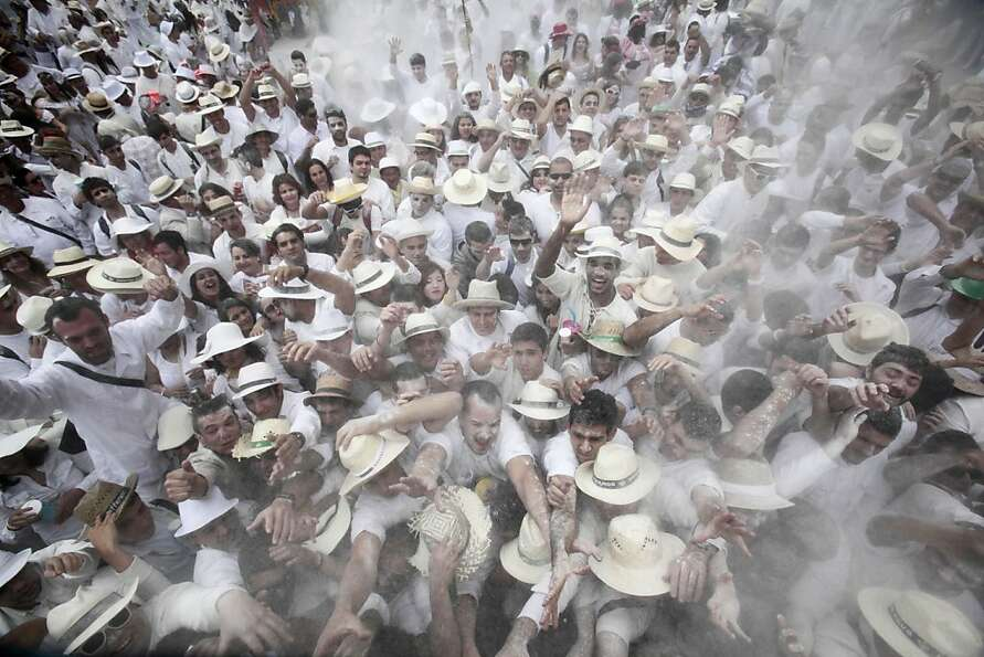 Powder to the people! White-hatted revelers throw talcum at one another during the carnival o