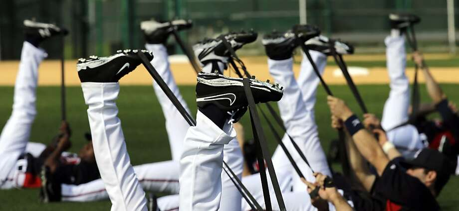 A site for sore thighs: The Atlanta Braves' boys of summer use rubber bands to stretch out their winter legs at spring training in Kissimmee, Fla. Photo: David J. Phillip, Associated Press