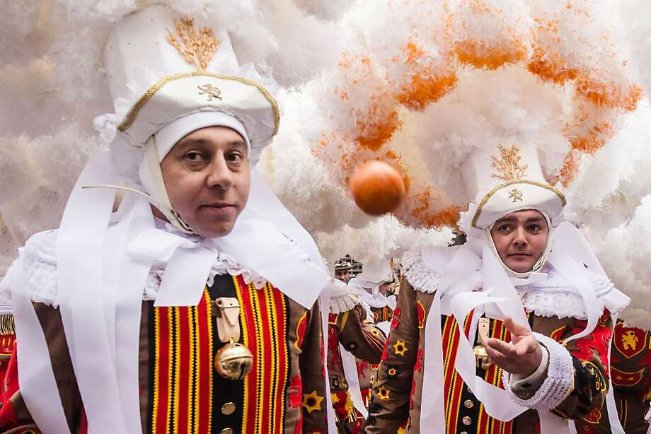 Have an orange:A Gilles of Binche throws fruit at a spectator during carnival in Binche, Belgium. As many as 1,000 of the clown-like Gilles gathered in the city center of Binche, wearing ostrich feather hats and black medieval costumes hung with bells and decorated with fluffy lace. The oranges are considered a gift of good luck, and it is an insult to throw them back. Photo: Geert Vanden Wijngaert, Associated Press
